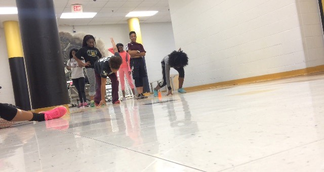 Members of the girls core track team practicing their sprints in the hallway.