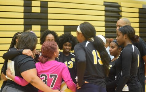 Members of the volleyball team huddle during the senior night game.